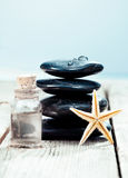 Spa massage stones with essential oil. Balanced column of smooth black spa massage stones with a bottle of essential oil ready for a luxurious hot rock massage stock photography