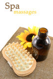 Spa massage tools. Aromatic oil and wooden massage brush on brown mat Royalty Free Stock Photography