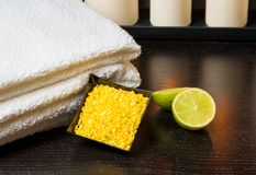 Spa massage with towel stacked white candles sea salt and lime Stock Image
