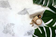 Spa and massage treatments on white, marble background monstera leaves. royalty free stock images