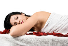 Spa massage woman. Woman lying on massage table  with eyes closed at spa retreat seen from profile isolated on white background,more spa photos in Spa Royalty Free Stock Images