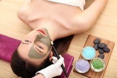 Spa massage for woman with facial mask on face.  Royalty Free Stock Image