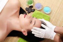 Spa massage for woman with facial mask on face.  Stock Photos