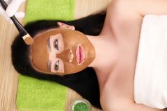 Spa massage for woman with facial mask on face.  Stock Image