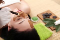 Spa massage for woman with facial mask on face.  Stock Images