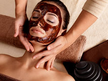 Spa massage for woman with facial mask on face. Spa massage for young woman with facial mask on face - indoors Royalty Free Stock Images