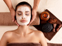 Spa massage for woman with facial mask on face. Spa massage for young woman with facial mask on face - indoors Royalty Free Stock Image