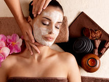 Spa massage for woman with facial mask on face. Spa massage for young woman with facial mask on face - indoors royalty free stock photography