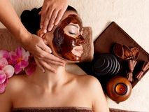 Spa massage for woman with facial mask on face. Spa massage for young woman with facial mask on face - indoors Stock Images