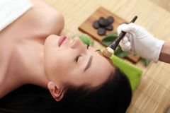 Spa massage for woman with facial mask on face.  Stock Photo