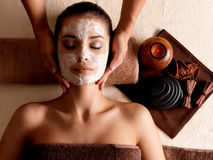 Spa massage for woman with facial mask on face. Spa massage for young woman with facial mask on face - indoors Stock Photo