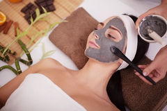 Spa massage for young woman with facial mask on face - indoors Stock Photo