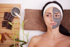 Spa massage for young woman with facial mask on face - indoors Royalty Free Stock Image
