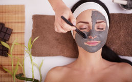 Spa massage for young woman with facial mask on face - indoors Royalty Free Stock Photos