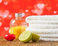 Spa massagegräns med den handduk staplad röd stearinljuset och limefrukt för valentindag Arkivfoton