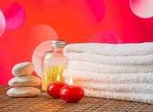 Spa massagegräns med staplade röda stearinljus för handduk och stenen för valentindag Arkivfoton