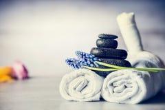 Spa massageinställning med handdukar, varma stenar och blåa blommor, slut upp, wellnessbegrepp Arkivbilder