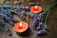 Spa massageinställning med lavendelblommor, parfymerade aromstearinljus på träbakgrund arkivfoton