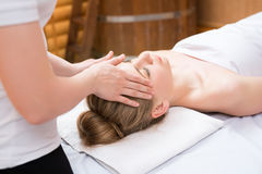 Spa. Masseuse put her hands on girl's face Stock Photography