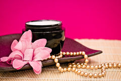 Spa moisturising cream with flower and necklace. Spa lotion cream with fashion accessories Royalty Free Stock Photography