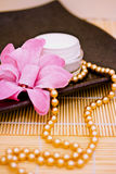 Spa moisturising cream with flower and necklace. Spa lotion cream with fashion accessories Royalty Free Stock Image