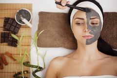 Spa Mud Mask. Woman in Spa Salon. Face Mask. Facial Clay Mask. T. Applying facial mask at woman face at beauty salon Stock Images