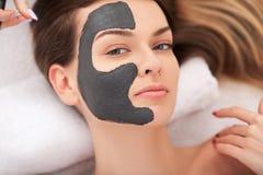 Spa Mujer divertida atractiva con una máscara de la arcilla en su cara Foto de archivo