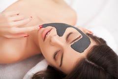 Spa Mujer divertida atractiva con una máscara de la arcilla en su cara Imagenes de archivo