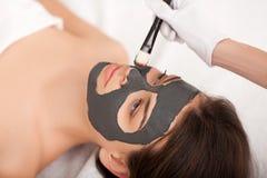 Spa Mujer divertida atractiva con una máscara de la arcilla en su cara Fotos de archivo