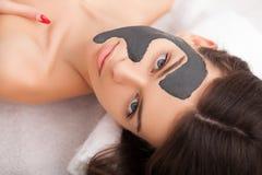 Spa Mujer divertida atractiva con una máscara de la arcilla en su cara Imagen de archivo libre de regalías