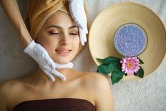 Spa Mujer joven en la tabla del masaje en salón del balneario de la belleza Fotografía de archivo