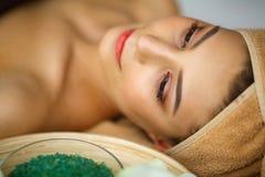 Spa Mujer joven en la tabla del masaje en salón del balneario de la belleza Fotos de archivo