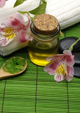 Spa objects. Bath salt and white orchid with essential oil on green mat Stock Photography
