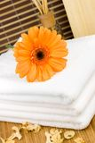 Spa objects. Orange flower on a white towels Royalty Free Stock Photography