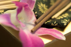 Spa objects. Incense burning over orchid flowers Royalty Free Stock Photo