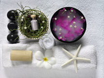 Spa objects. Stoneswith flowers on white towels Royalty Free Stock Photography