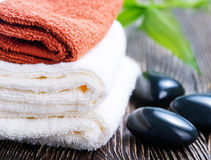 SPA objects. Clear towels, black stones and bamboo on a table Stock Photo