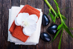 SPA objects. Clear towels, black stones and bamboo on a table Royalty Free Stock Photography