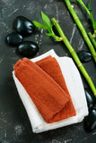SPA objects. Clear towels, black stones and bamboo on a table Stock Photos