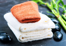 SPA objects. Clear towels, black stones and bamboo on a table Royalty Free Stock Photo