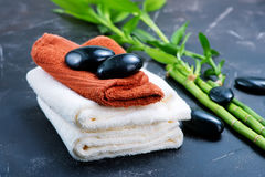 SPA objects. Clear towels, black stones and bamboo on a table Royalty Free Stock Images