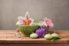 Spa och wellnessbegrepp med blommor i bunkar och stearinljus på trätabellen royaltyfri foto