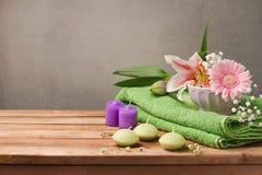 Spa och wellnessbegrepp med den nya handduken, stearinljus och blommor på trätabellen över lantlig grå bakgrund arkivbild