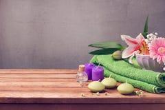 Spa och wellnessbegrepp med den nya handduken, stearinljus och blommor på trätabellen fotografering för bildbyråer