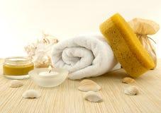 Spa och wellnessinställning med handduken, svamp, kräm, stearinljus och Royaltyfria Bilder