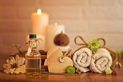 Spa och wellnessinställning med olja, stearinljus och handdukar royaltyfri fotografi