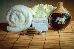 Spa Oil Massaging Treatment and Skincare Concept., Component of Therapy Massage With Plumeria or Frangipani Flowers, Towel, Stones. Aroma Candle and Oil on The royalty free stock photo