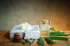 Spa Oil Massaging Treatment and Skincare Concept., Component of Therapy Massage With Plumeria or Frangipani Flowers, Towel, Stones. Aroma Candle and Oil on The royalty free stock photography