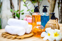 Spa oils in bottles on wooden table and nature background. Stock Photo