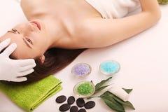 Spa Omsorgansiktsbehandling Får den unga kvinnan för skönhet en head massage i salongen royaltyfria foton